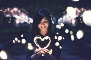 woman holding lit heart firework