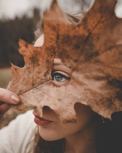woman looking through a hole in a leaf